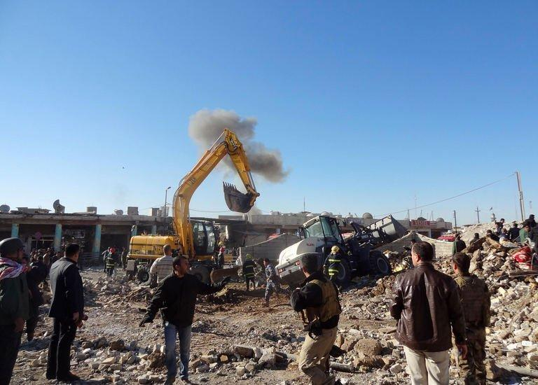 Local men inspect the site of an explosion in Kirkuk, Iraq, on January 16, 2013