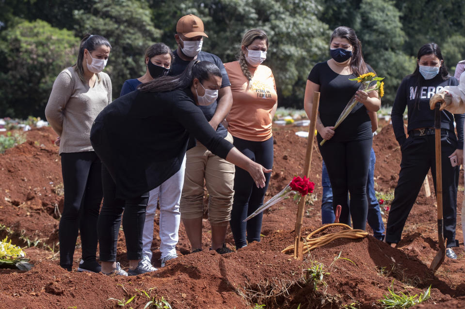 A woman throws a flower over the tomb of a relative who died from complications related to COVID-19 at the Vila Formosa cemetery in Sao Paulo, Brazil, Wednesday, April 7, 2021. (AP Photo/Andre Penner)