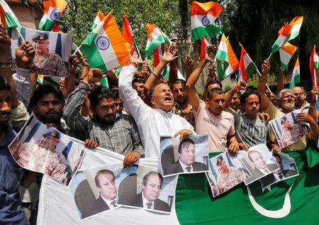 People shout slogans as they hold portraits of Pakistan's Prime Minister Nawaz Sharif and Pakistan's army chief Lieutenant General Qamar Javed Bajwa during a protest organized by Shiv Sena, a Hindu hardline group, in Jammu, May 2, 2017, against the killing of two Indian soldiers who were patrolling the de facto border in the disputed Kashmir region on Monday. REUTERS/Mukesh Gupta