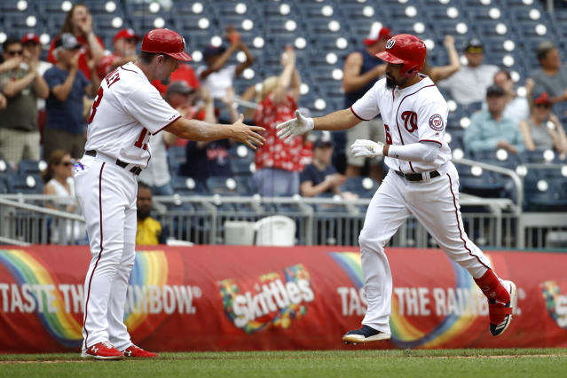 Washington Nationals' Anthony Rendon, right, rounds the bases on a solo home run past third base coach Bob Henley in the seventh inning of the first baseball game of a doubleheader against the Colorado Rockies, Wednesday, July 24, 2019, in Washington. Washington won 3-2. (AP Photo/Patrick Semansky)