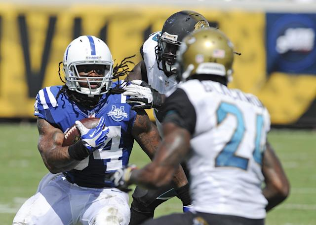 FILE - In this Sept. 29, 2013 file photo, Indianapolis Colts running back Trent Richardson, left, looks for an opening around Jacksonville Jaguars cornerback Will Blackmon (24) during the first half of an NFL football game in Jacksonville, Fla. (AP Photo/Stephen Morton, File)