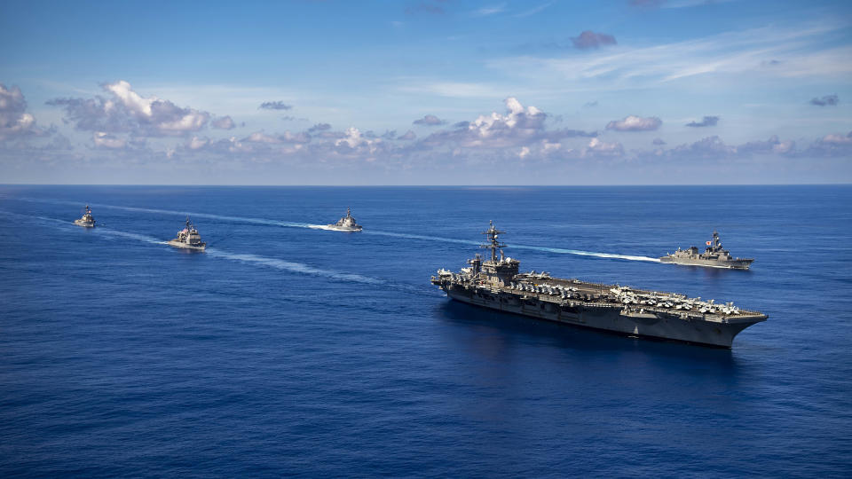 In this photo released by the U.S. Navy, the Nimitz-class aircraft carrier USS Carl Vinson (CVN 70), the Ticonderoga-class guided-missile cruiser USS Lake Champlain (CG 57), and the Arleigh Burke-class guided-missile destroyer USS Chafee (DDG 90) conduct a passing honors ceremony with the Japan Maritime Self-Defense Force (JMSDF) Murasame-class destroyer JS Ikazuchi (DD 107) and the Kongo-class guided-missile destroyer JS Chokai (DDG 176) in the Pacific Ocean, Sept. 19, 2021. A spate of recent Chinese military flights off Taiwan, which Beijing claims as its own, and naval maneuvers by the United States and its allies to reinforce maritime routes challenged by China are fueling increasing tensions in a region already on edge. (Haydn N. Smith/U.S. Navy via AP)