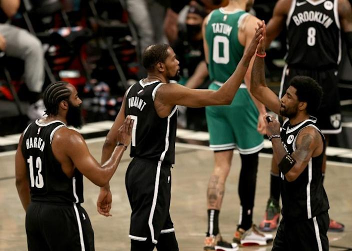Brooklyn's Kyrie Irving is congratulated by teammates Kevin Durant and James Harden during the Nets' 104-93 NBA playoff victory over the Boston Celtics