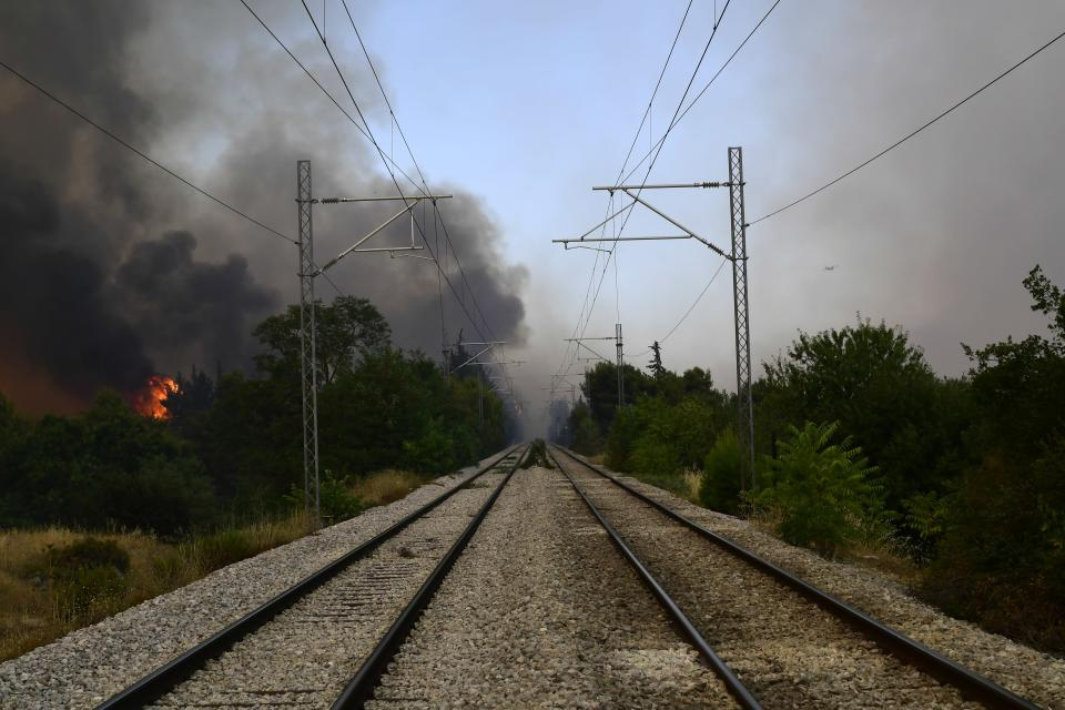 Flames burn near the railway lines during a wildfire in Tatoi area, northern Athens, Greece, Tuesday, Aug. 3, 2021. Hundreds of residents living near a forest area north of Athens fled their homes Tuesday as a wildfire reached residential areas as Greece grappled with its worst heatwave in decades. (AP Photo/Michael Varaklas)
