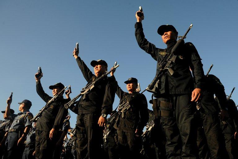 Philippine police hold up their firearms during a ceremony in Manila, on December 29, 2012