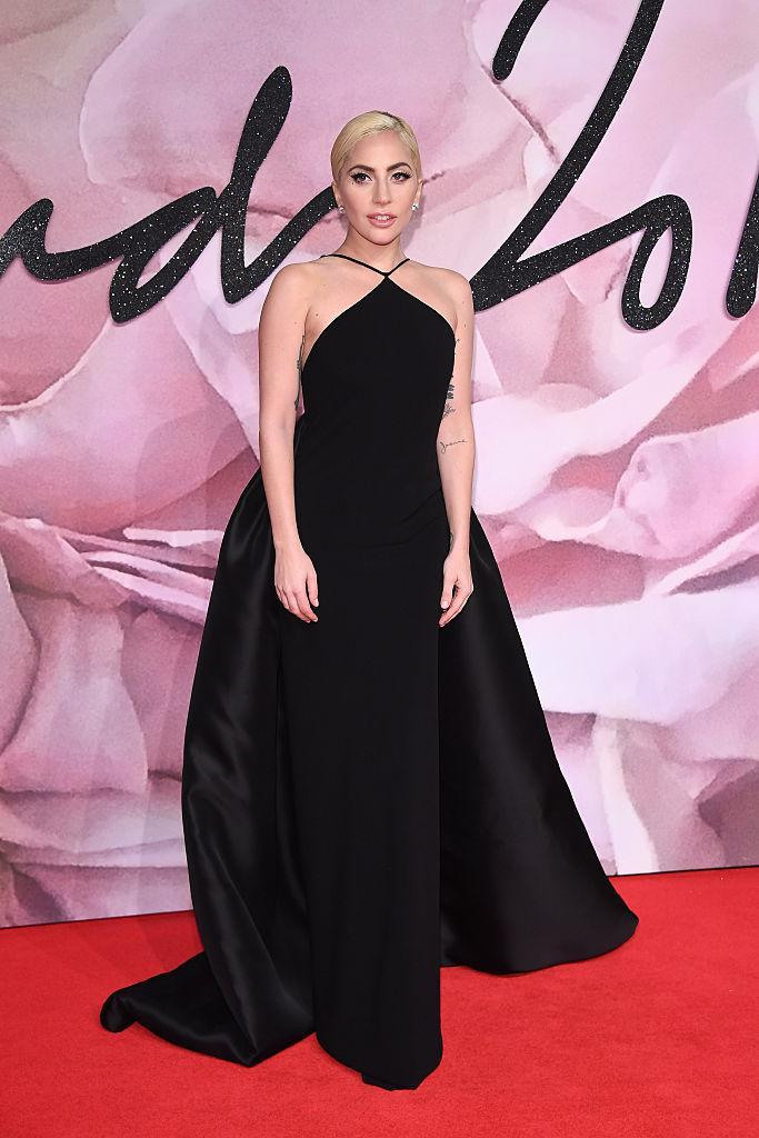 <p>The singer wore a black satin halter neck gown that had a long train made just for her by designer, stylist, and friend Brandon Maxwell. She opted for a sleek bun as the finishing touch for her look. (Photo: Getty Images) </p>