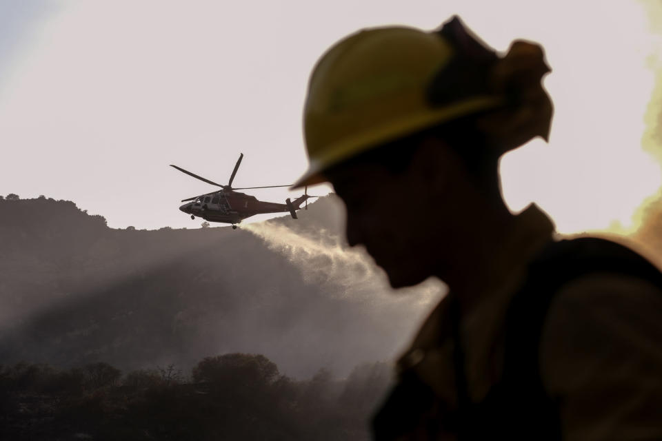 A firefighter keeps watch as a firefighting helicopter drops water on a brush fire scorching at least 100 acres in the Pacific Palisades area of Los Angeles on Saturday, May 15, 2021. (AP Photo/Ringo H.W. Chiu)