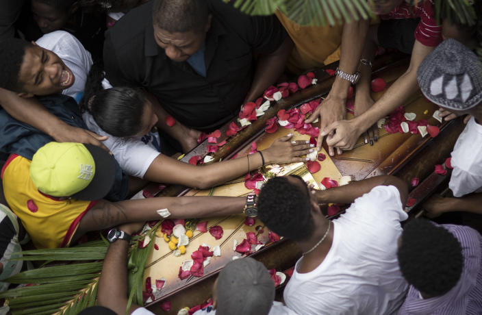 Relatives and friends of Douglas Rafael da Silva Pereira mourn around his coffin during his burial in Rio de Janeiro, Brazil, Thursday, April 24, 2014. A protest followed the burial of Pereira, whose shooting death sparked clashes Tuesday night between police and residents of the Pavao-Pavaozinho slum. (AP Photo/Felipe Dana)