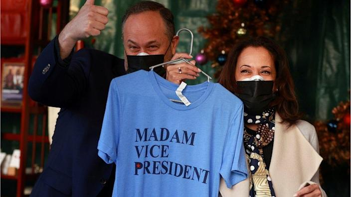 Kamala Harris holds a t-shirt that reads Madam Vice President, while standing next to her husband Doug Emhoff