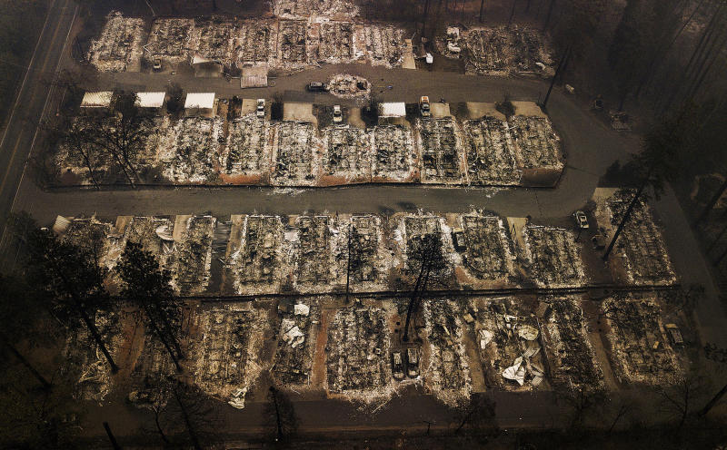 "FILE - This Nov. 15, 2018, aerial file photo, shows the remains of residences leveled by the Camp Fire in Paradise, Calif. A federal bankruptcy court judge on Wednesday, Nov. 27, 2019, rejected Pacific Gas & Electric's latest attempt to change a California law requiring utilities to pay for the devastation from wildfires ignited by their electrical equipment. The decision issued by U.S. Bankruptcy Judge Dennis Montali preserves a long-standing principle known as ""inverse condemnation."" (AP Photo/Noah Berger, File)"