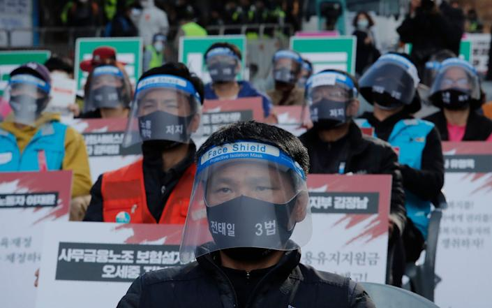Workers wearing face masks and shields to help protect against the spread of the coronavirus attend a rally to demand better working conditions in Seoul - AP
