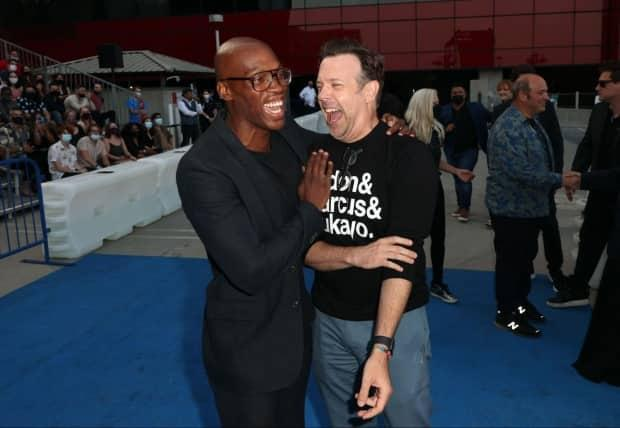 Montreal actor Moe Jeudy-Lamour, left, and Jason Sudeikis attend the season two premiere of Apple TV's Ted Lasso on July 15, 2021 in West Hollywood, Calif.  (Kevin Winter/Getty Images - image credit)