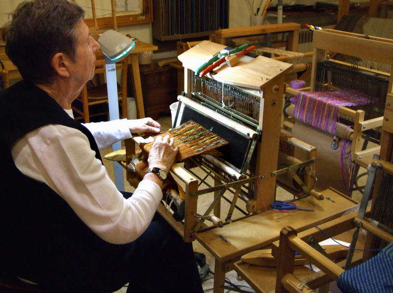 In this 2011 photo provided by the Fellowship Community, Pearl Zucherman, a member of the Fellowship Community, works on a loom in the weavery of the Fellowship, a commune-like setting in Chestnut Ridge, N.Y., that takes an unusual approach to care of the elderly. Situated on a hilltop in suburban Rockland County, Fellowship looks a bit like a village out of the past. Besides the weavery there is a farm a pottery and candle shop, a dairy barn with 10 cows, a print shop, a metal shop, food gardens and a wood shop where residents are urged to contribute to the community by lending a hand. (AP Photo/Fellowship Community, Miklos Gratzer)