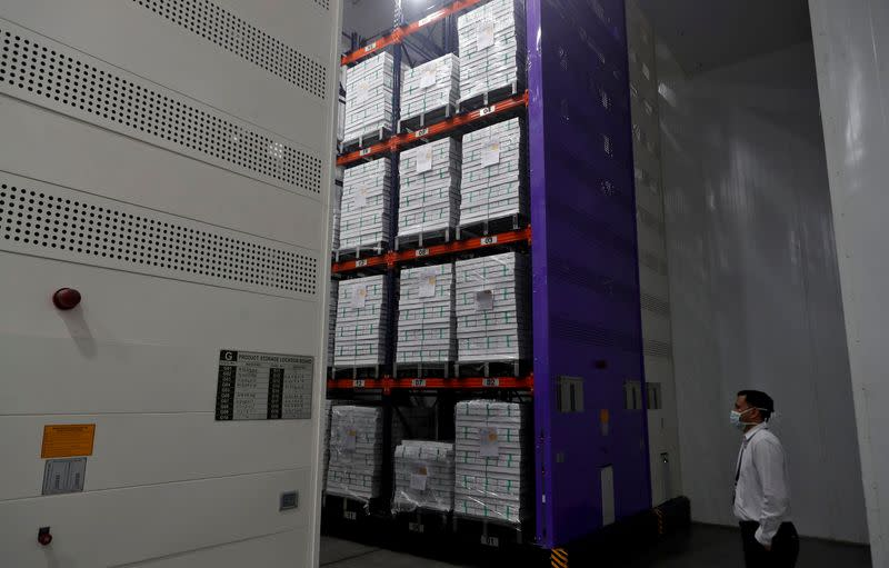 FILE PHOTO: A man wearing a protective mask stands next to boxes containing the vials of AstraZeneca's COVISHIELD, coronavirus disease (COVID-19) vaccine, inside a cold room at the Serum Institute of India, Pune