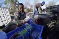 FILE - In this Feb. 22, 2021, file photo, Madonna Manor maintenance supervisor Lamar Jackson left, stacks bottled water brought by Mac Epps of Mississippi Move, as part of the supply efforts by city councilman and State Rep. De'Keither Stamps to a senior residence in west Jackson, Miss. The snow and ice that crippled some states across the South has melted. But it has exposed the fragility of aging waterworks that experts have been warning about for years. Cities across Texas, Tennessee, Louisiana and Mississippi are still grappling with outages that crippled health care facilities and forced families to wait in line for potable water. (AP Photo/Rogelio V. Solis)