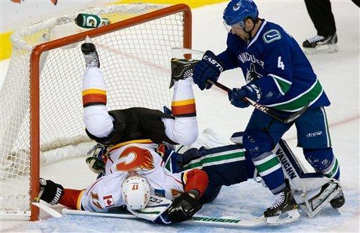 Calgary Flames' Blake Comeau, left, crashes into Vancouver Canucks goalie Cory Schneider as Canucks' Keith Ballard, right, watches during the second period an NHL hockey game game in Vancouver, British Columbia, on Wednesday, Jan. 23, 2013. (AP Photo/The Canadian Press, Darryl Dyck)