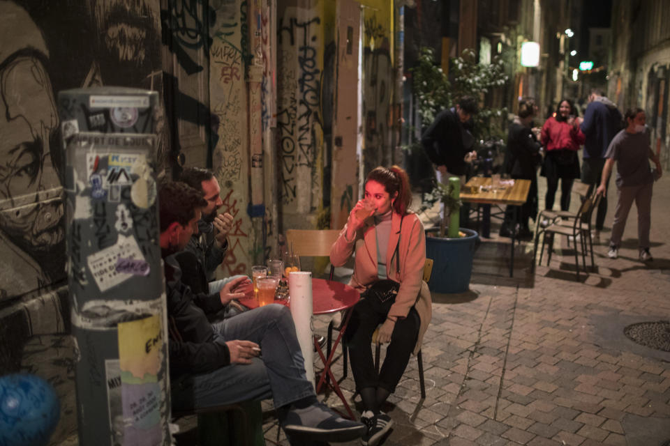 Friends share a drink at a bar before curfew in Marseille, southern France, Sat, Oct. 24, 2020. The curfew imposed in eight regions of France last week, including Paris and its suburbs, is being extended to 38 more regions and Polynesia. (AP Photo/Daniel Cole)