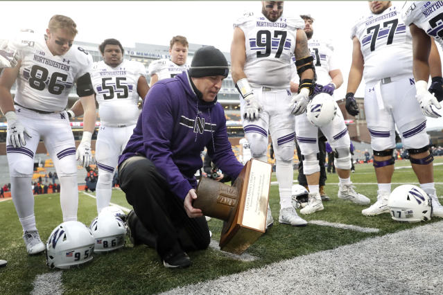 Northwestern head coach Pat Fitzgerald picks up the Land of Lincoln trophy after an NCAA college football game against Illinois, Saturday, Nov. 30, 2019, in Champaign, Ill. Northwestern won 29-10. (AP Photo/Charles Rex Arbogast)