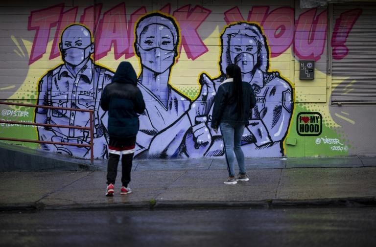 Two woman stand in front of a mural by artist @Dister picturing first responders with masks on and a Thank You message during the novel coronavirus pandemic in the Harlem neighbourhood of Manhattan in New York City (AFP Photo/Johannes EISELE)