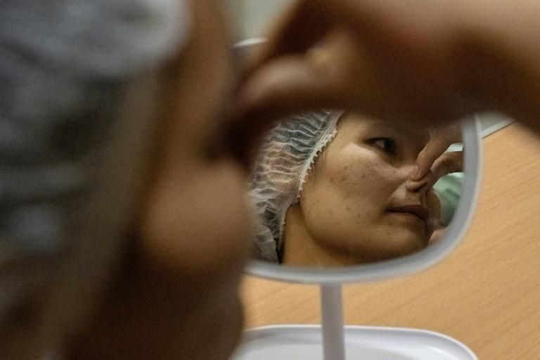 """All my friends called me flat-nose,"" said Somprasong Aimsantia as she waiting to undergo surgery to install a silicone bridge"