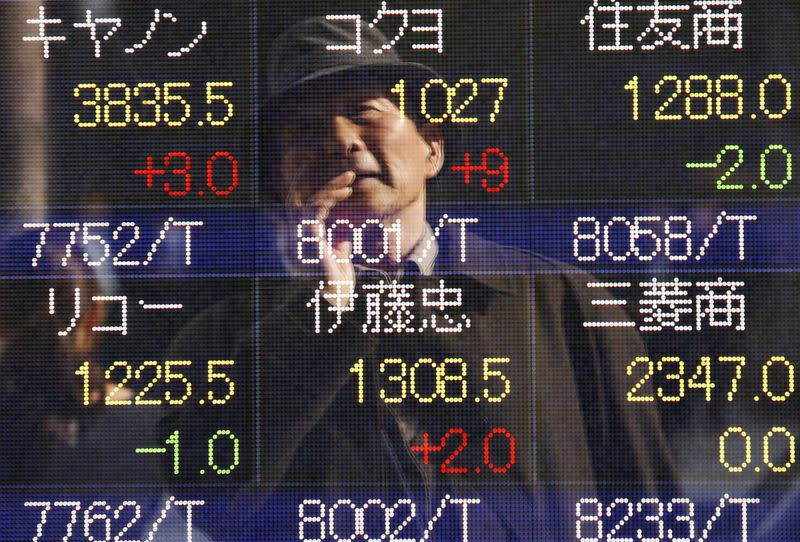 A pedestrian is reflected on an electronic board showing various stock prices, in Tokyo