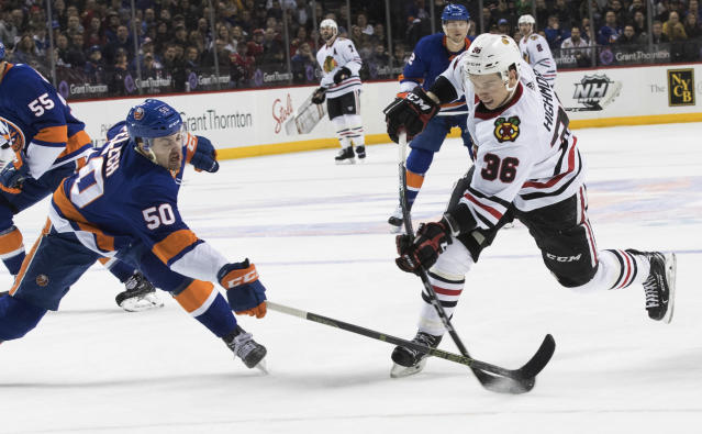 Chicago Blackhawks center Matthew Highmore (36) shoots past New York Islanders defenseman Adam Pelech (50) during the first period of an NHL hockey game Saturday, March 24, 2018, in New York. (AP Photo/Mary Altaffer)