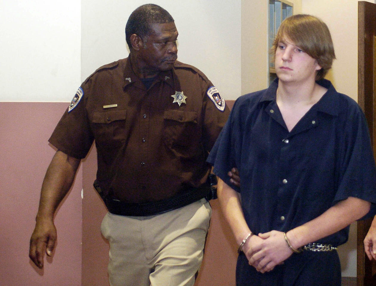 In this July 18, 2011 photograph, Hinds County Sheriff's deputy Lawyer Smith, left, escorts murder suspect John Aaron Rice, of Brandon, to a preliminary hearing at the Hinds County Courthouse in Jackson, Miss. The murder charge against Rice was reduced to simple assault stemming from his involvement in a June hit-and-run death of James Craig Anderson, 49, of Jackson. Deryl Dedmon, also of Brandon, was charged in the death of Anderson. (AP Photo/The Clarion-Ledger, Greg Jenson) NO SALES