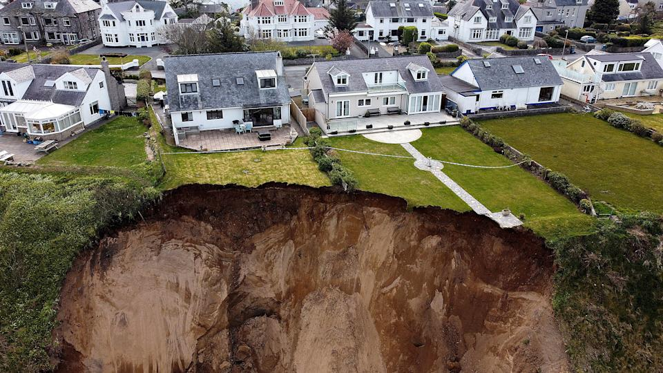 Houses are seen on the edge of a cliff after it collapsed in the village of Nefyn, Wales, Britain, April 20, 2021. Picture taken with a drone. REUTERS/Carl Recine     TPX IMAGES OF THE DAY