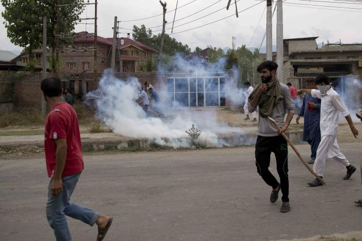 Kashmiris take cover from tear gas shells during a protest after Friday prayers in Srinagar, Indian controlled Kashmir, Friday, Aug. 9, 2019. A strict curfew in Indian-administered Kashmir in effect for a fifth day was eased Friday to allow residents to pray at mosques, officials said, but some protests still broke out in the disputed region despite thousands of security forces in the streets as tensions remained high with neighboring Pakistan. (AP Photo/ Dar Yasin)