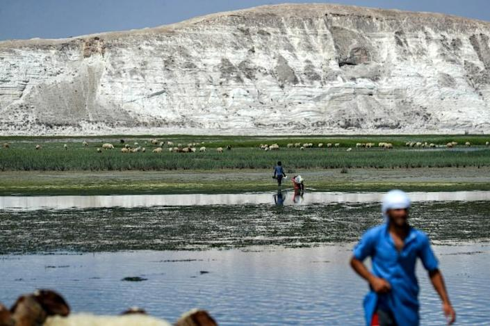 People walk through what was the Euphrates riverbed near the Syrian village of Rumayleh (AFP/Delil SOULEIMAN)