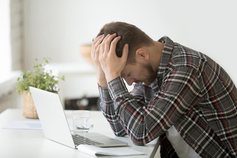 A man in a plaid shirt puts his head in his hands in anguish sitting in front of his laptop.