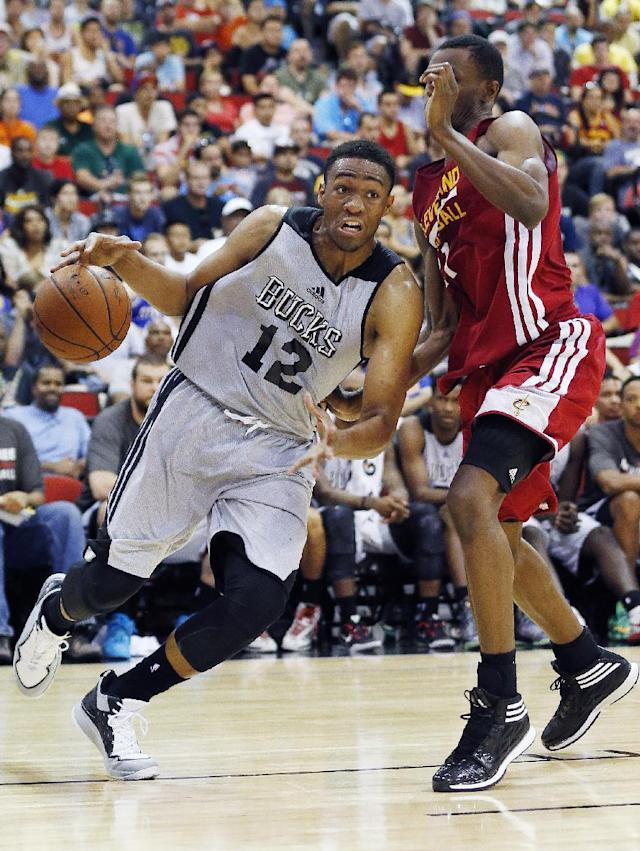 Jabari Parker of the Milwaukee Bucks drives by Andrew Wiggins of the Cleveland Cavaliers in an NBA summer league basketball Friday, July 11, 2014, in Las Vegas