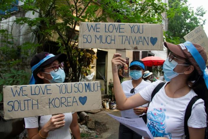 Demonstrators carry placards as they march during a protest against military coup, in Yangon