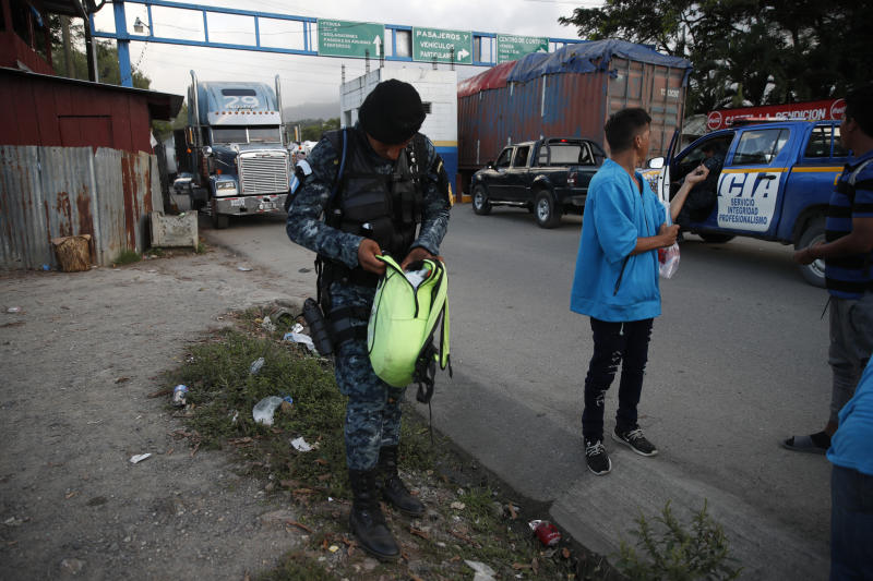 Guatemalan National Police agents check a backpack of a Honduras migrant trying to reach the United States at El Cinchado, Guatemala, in the border with Honduras, Wednesday, Jan. 15, 2020. Hundreds of mainly Honduran migrants started walking and hitching rides Wednesday from the city of San Pedro Sula and crossed the Guatemala border in a bid to form the kind of migrant caravan that reached the U.S. border in 2018. (AP Photo/Moises Castillo)