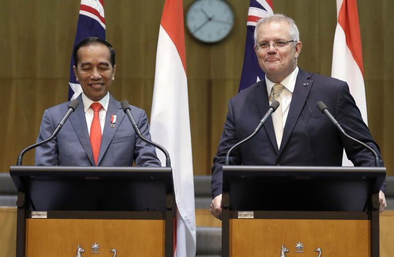 Indonesia's President Joko Widodo, left, and Australia's Prime Minister Scott Morrison share a laugh as they give a joint statement at Parliament House in Canberra, Monday, Feb. 10, 2020. Widodo is on a two-day visit to Canberra, his fourth visit to Australia. (AP Photo/Rick Rycroft, Pool)