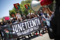 FILE - In this Friday, June 19, 2020, file photo, demonstrators protest during a Juneteenth rally at the Brooklyn Museum, in the Brooklyn, N.Y. President Joe Biden signed into law Thursday, June 17, 2021, a bill designating Juneteenth—which commemorates June 19, 1865 when enslaved people in Texas learned they had been freed—as the 11th federal holiday. (AP Photo/John Minchillo, File)