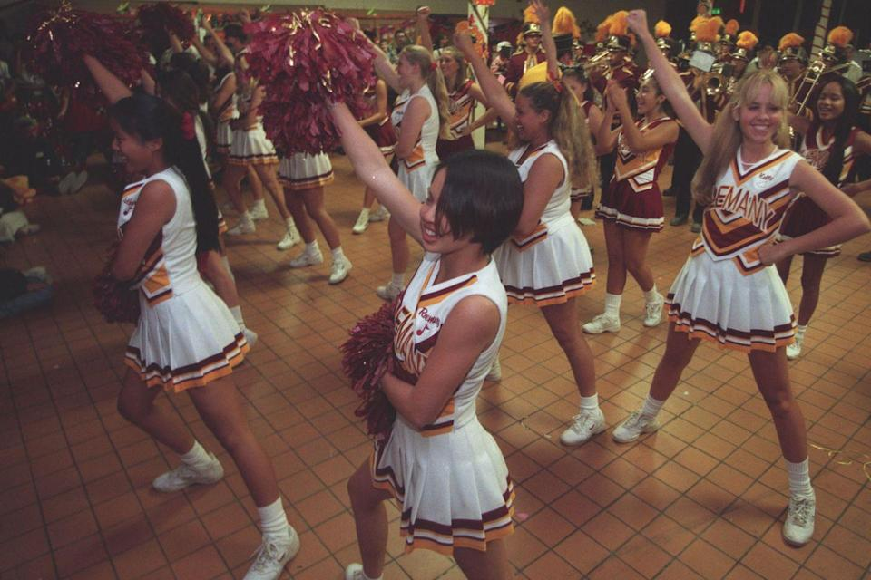 <p>The cheerleading squad and marching band entertain the crowd at a Halloween dance at a California high school. </p>
