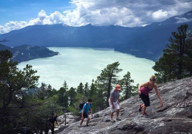 People climb up a rock face towards the first peak on the Stawamus Chief mountain above the waters of Howe Sound. After five years of campaigning, the region was designated a UNESCO biosphere region on Wednesday. (Darryl Dyck/Canadian Press - image credit)