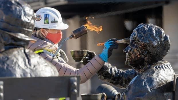 A worker wearing a mask applies wax to the Women are Persons! sculptures in front of the temporary Senate building in downtown Ottawa on April 6, 2021. The sculpture was relocated while Centre Block is being renovated. (Andrew Lee/CBC - image credit)