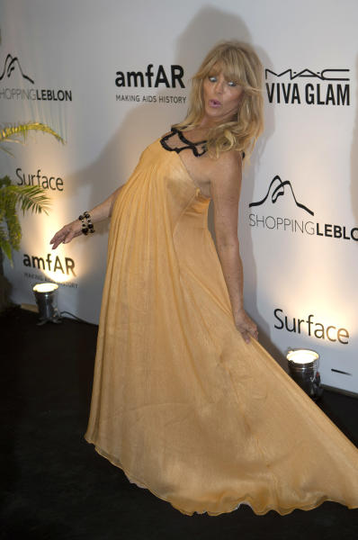 U.S. actress Goldie Hawn jokes as designer Kenneth Cole accidentally steps on her dress as they arrive to a charity dinner for amfAR, a foundation for AIDS research in Rio de Janeiro, Brazil, Friday, Oct. 4, 2013. (AP Photo/Silvia Izquierdo)