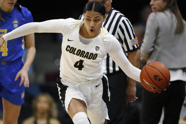 Colorado guard Lesila Finau, center, scoops up the ball as UCLA guard Lindsey Corsaro, left, pursues in the first half of an NCAA college basketball game Sunday, Jan. 12, 2020, in Boulder, Colo. (AP Photo/David Zalubowski)