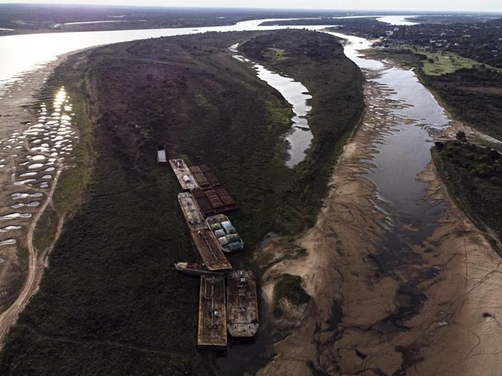 Barges lay stranded next to one of the branches of the Paraguay river that has gone dry, in Lambare, Paraguay, on 14 September.