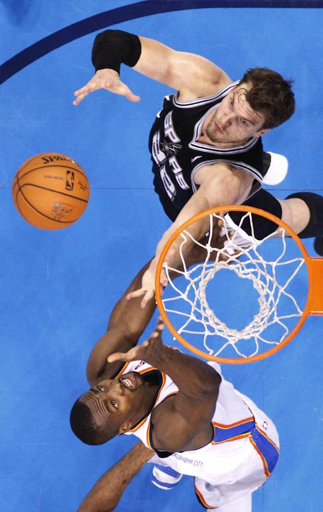 San Antonio Spurs center Tiago Splitter (22) and Oklahoma City Thunder forward Serge Ibaka reach for a rebound in the second quarter of Game 4 of the Western Conference finals NBA basketball playoff series in Oklahoma City, Tuesday, May 27, 2014. (AP Photo/Sue Ogrocki)