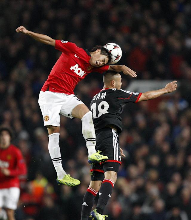 Manchester United's Shinji Kagawa, left, and Bayer Leverkusen's Sidney Sam contest a header during their Champions League Group A soccer match at Old Trafford in Manchester, England, Tuesday Sept 17, 2013. (AP Photo/Jon Super)