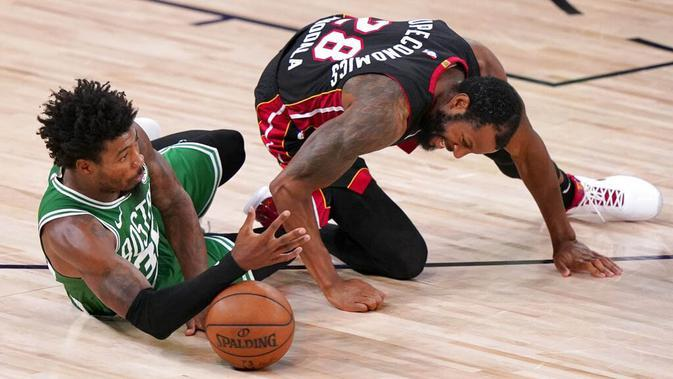 Pebasket Boston Celtics, Marcus Smart, berebut bola dengan pebasket Miami Heat, Andre Iguodala, pada gim keempat final NBA Wilayah Timur di AdventHealth Arena, Kamis (24/9/2020). Miami Heat menang dengan skor 109-112. (AP/Mark J. Terrill)