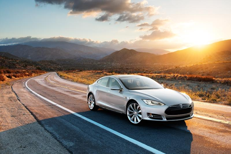 A silver Tesla Model S driving on a road, with hills in the background.