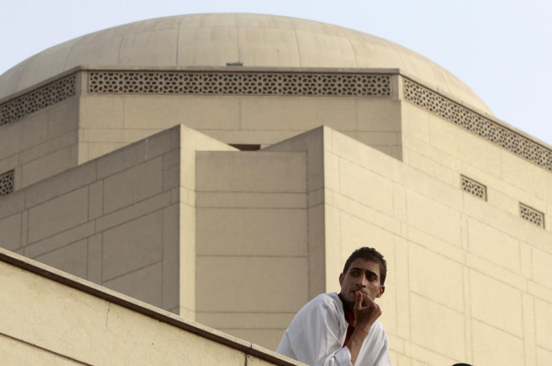 An Egyptian worker perches on the roof of the Cairo Opera House during a protest to support Enas Abdel-Dayem, head of the Cairo Opera House, not pictured, demanding the resignation of Egyptian culture minister at the opera house garden in Cairo, Egypt, Thursday, May 30, 2013. The Cairo Opera House has become a new battleground between supporters and opponents of Egypt's Islamist president, this time fighting over the direction of the Middle East's oldest music institution. The new culture minister fired the opera's head in what he calls a campaign to bring in new blood across the artistic scene. But her staff refuse any new boss and have closed the curtain on all performances, accusing the minister of bending to Islamist pressure. (AP Photo/Amr Nabil)