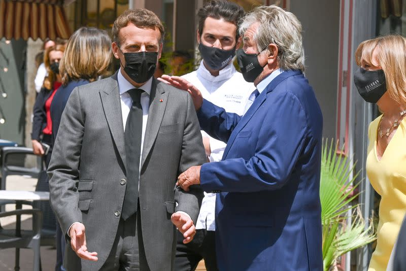 French President Emmanuel Macron talks with restaurant owner Michel Chabran as he arrives for a lunch in Valence