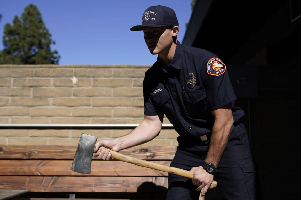Fire engine probationary firefighter Cole Gomoll of Los Angeles County Fire Department - Station 106 demonstrates how to use a flathead ax at his station Friday, Feb. 26, 2021, in Rancho Palos Verdes, Calif, a suburb of Los Angeles. He used the ax to cut away the windshield of a vehicle crashed by golfer Tiger Woods on Tuesday. (AP Photo/Ashley Landis)