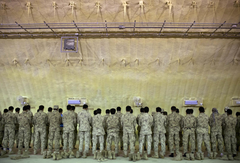 In this Thursday, Oct. 18, 2012 photo, members of Afghanistan's elite Civil Order Police line up for prayers inside a cavernous dome shaped building constructed by U.S, contractors to house the 3rd Battallion, at their base in Marjah, southern Helmand province, Afghanistan. As the U.S. and NATO close out their mission in Afghanistan preparing for the final withdrawal of combat troops by the end of 2014, the worry looms large that fresh outbursts of ethnically motivated fighting would send the country into a spiral of chaos and violence. (AP Photo/Anja Niedringhaus)